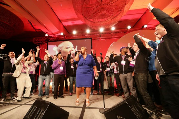 Frenchie Davis performs and the Task Force staff dances on stage.