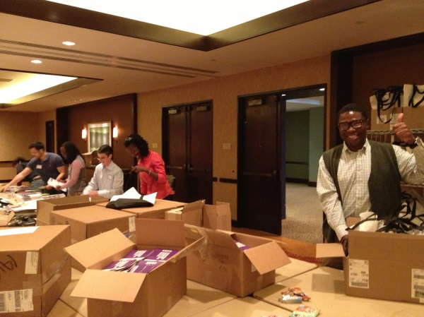 Volunteers stuffing bags for attendees.