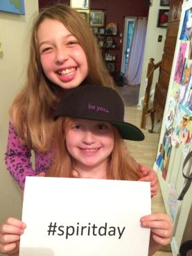 "2 children, Dayton and Saunder, wearing purple and a ""be you."" hat holding a sign that says #SpiritDay"